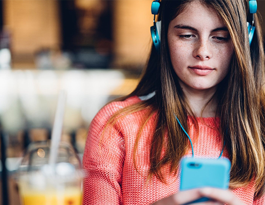 Woman Wearing Blue Headphones Listens To A Podcast While Looking At Her Phone
